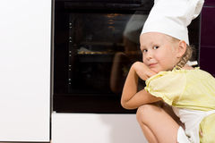 petite-fille-observant-sa-pizza-faite-maison-faire-cuire-43402318